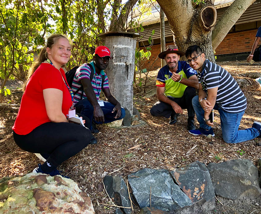 India Owen, Jeet Mukherjee and Alex Monona all with Leslie Lowe examine a native bee hive at the Botanic Gardens, learning about Indigenous land management.