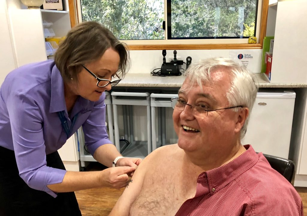 Registered nurse Barbara Coyne administers a flu jab vaccination to Dr Brad Murphy at Ashfield Country Practice