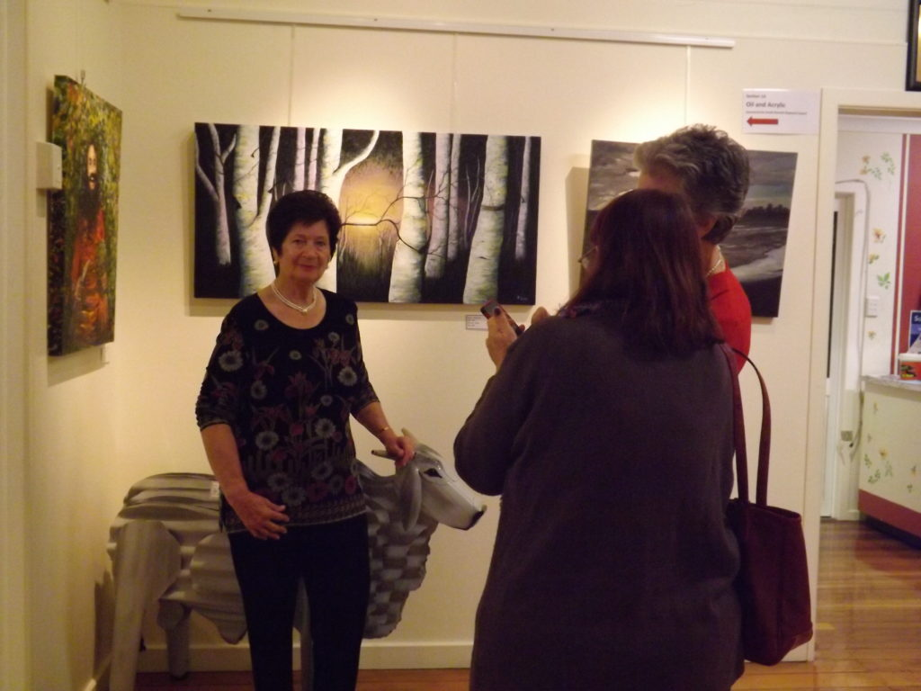 Rozalija Lear with one of her landscape paintings at a recent exhibition.