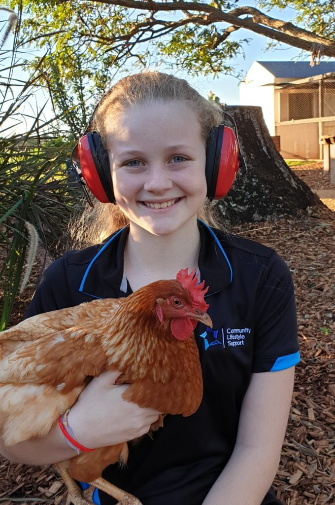 Summer with a pair of headphones she purchased for community use.