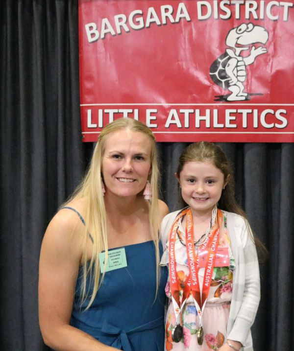 Taryn Gollshewsky shares her recent medals with young athlete Mia Edwards at the Bargara Little Aths 25th anniversary.