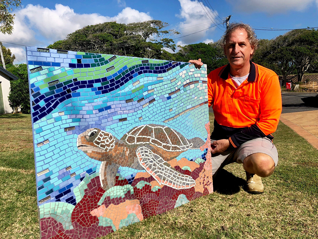 Paul Perry and his original mosaic artwork that now sits on the wall of the public amenity block at Archies in Bargara.