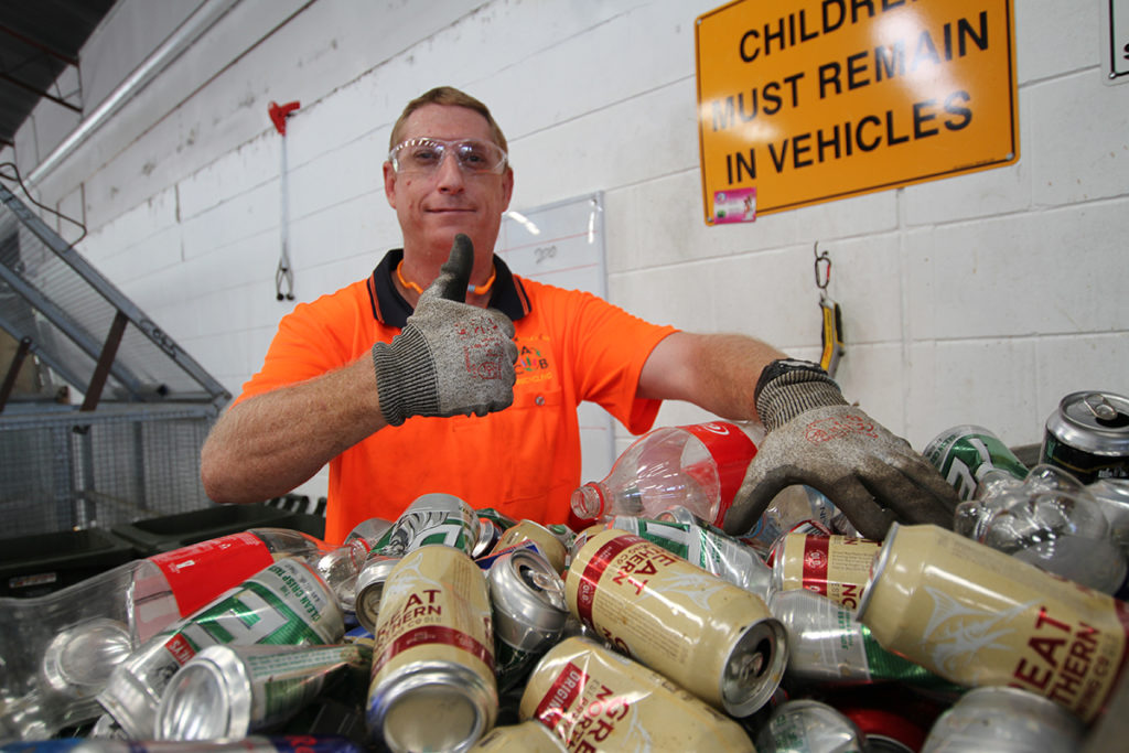 Chad Castles sorting through cans and bottles at ABC Recycling.
