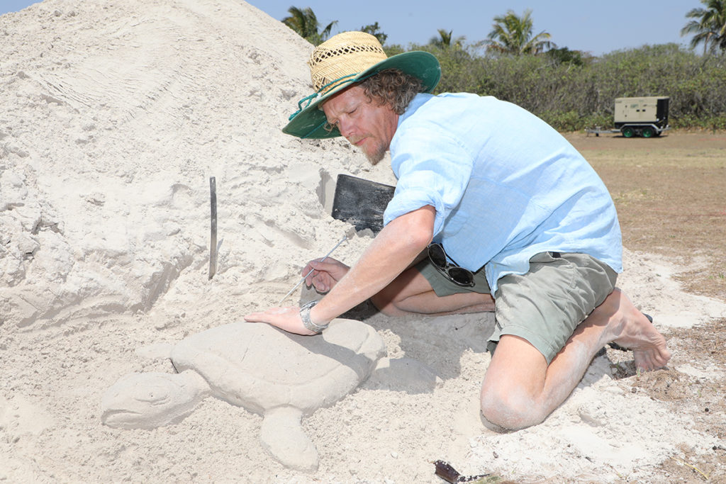 Arron McCormick sand sculpting at Bargara for tomorrow's Turtle Art Walk and Family Fun Day.