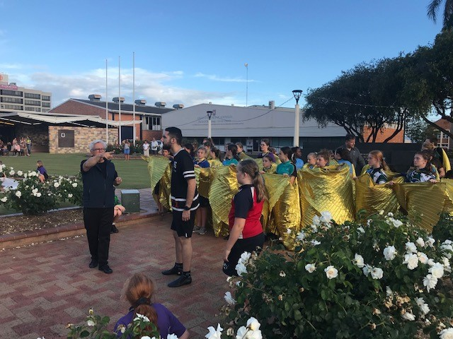 The Milbi Festival student performers rehearsing in Buss Park with Bundaberg Regional Council's Trevor Green and Robert McLellan.