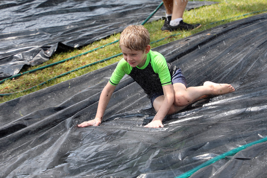 Dallas Walker hits the slippery slide at the water play event in Childers.