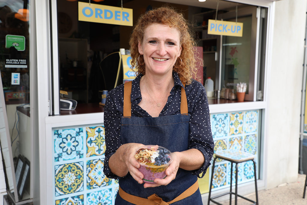 Owner Judy Plath outside Street Bean Coffee Bar with a  smoothie bowl.