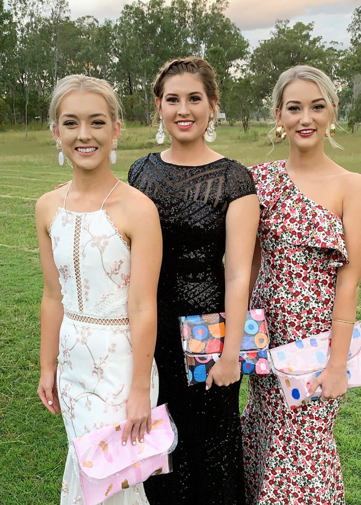 Chloe Johnson (far right) at the Gin Gin Show Ball last year with friends Emily Parsons and Makayla Chapman. All three are carrying clutches designed and made by Chloe.