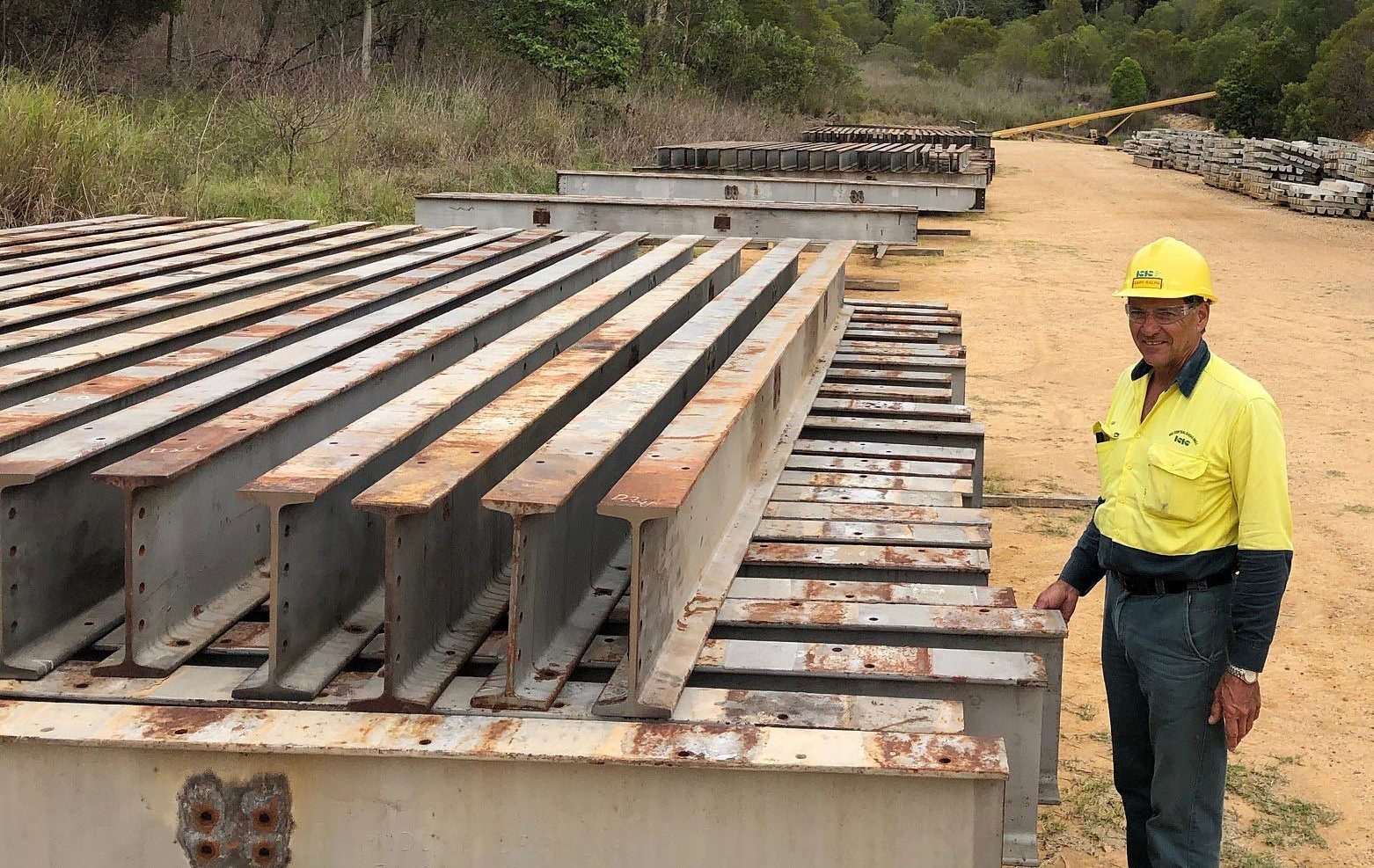 Mill supervisor Gary Ralph with steel recovered from bridges along the decommissioned Hughenden to Winton rail line which is being used in the Isis Mill cane rail line project. Also pictured is a stockpile of concrete sleepers manufactured at the Mill.