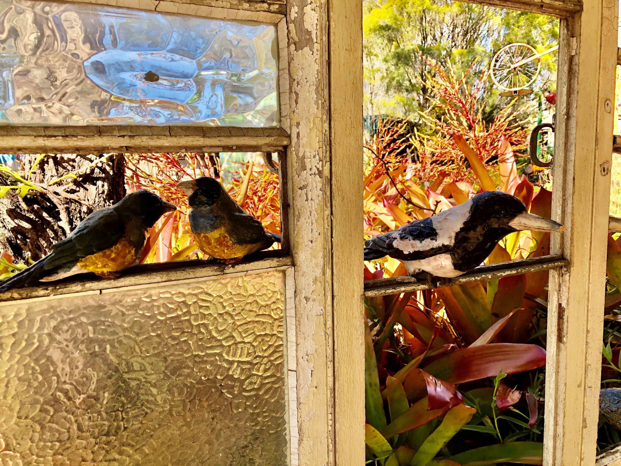 Ceramic birds make a lifelike scene as they perch on a window opening into Alice McLaughlin's gardens.