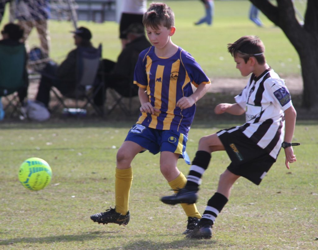 Bingera's Cooper Kelly (right) kicks the ball around an Across The Waves player in a recent under-9 game