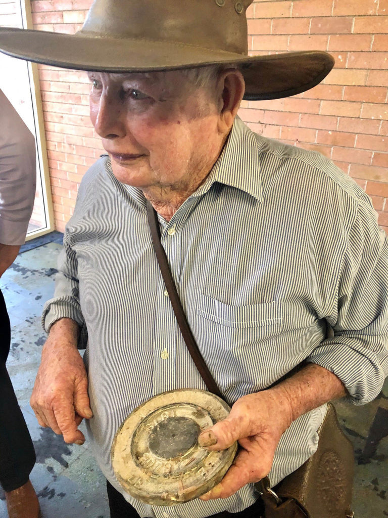 Former Kolan Shire Council worker Herb Aulfrey examines the cap from the time capsule which has been relocated from the soon-to-be-demolished Gin Gin Neighbourhood Centre. Herb assisted in burying the capsule in 1979.